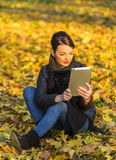 Woman with a Tablet in a Forest in the Autumn Stock Image