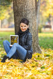 Woman with a Tablet in a Forest in the Autumn. Portrait of a young woman with a tablet sitting in a yellow autumn forest and looking to the camera Stock Photography