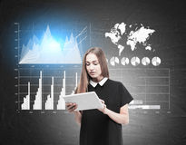 Woman with tablet and four graphs on blackboard Royalty Free Stock Photos