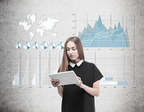 Woman with tablet and four graphs on concrete Stock Images