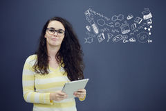 Woman with tablet in front of background with drawn business chart and icons. Royalty Free Stock Photos
