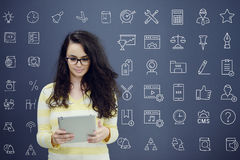 Woman with tablet in front of background with drawn business chart and icons. Stock Photos
