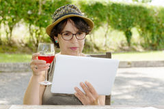Woman with a tablet and glass of wine in her garden Royalty Free Stock Photography