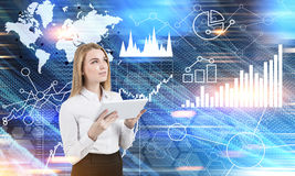 Woman with tablet and graphs in the air. Portrait of a blond businesswoman standing with a tablet in a blurred office with graphs in the air. Toned image Royalty Free Stock Image