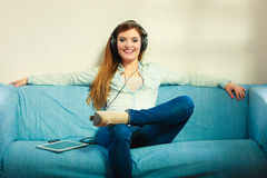 Woman with tablet headphones sitting on couch Stock Image