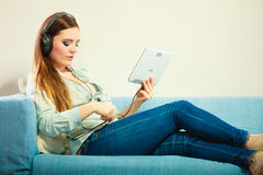 Woman with tablet headphones sitting on couch Royalty Free Stock Image