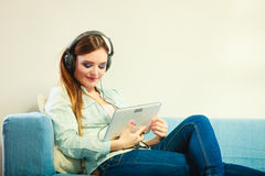 Woman with tablet headphones sitting on couch Royalty Free Stock Photos