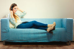 Woman with tablet headphones sitting on couch Stock Photography