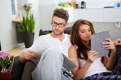 Woman with tablet and husband reading newspaper Royalty Free Stock Photo