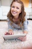 Woman with tablet lying on the carpet Stock Photography