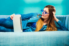 Woman with tablet lying on couch blue color Stock Photography