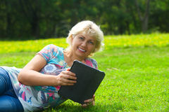 Woman with tablet lying on grass in park Stock Images