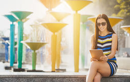Woman with tablet near fountain Royalty Free Stock Photos