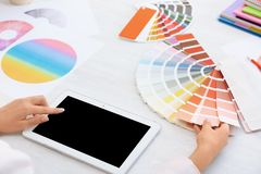 Woman with tablet and paint color palette samples. At table, closeup royalty free stock photo
