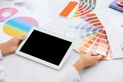 Woman with tablet and paint color palette samples. At table, closeup stock images