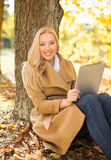 Woman with tablet pc in autumn park Royalty Free Stock Image