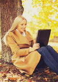 Woman with tablet pc in autumn park Stock Photos
