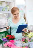 Woman with tablet pc and basket at flower shop Stock Photo