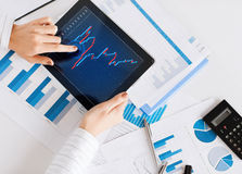 Woman with tablet pc and chart papers Stock Image