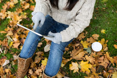 Woman with tablet pc and coffee in autumn park Royalty Free Stock Photography