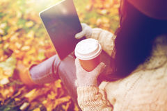 Woman with tablet pc and coffee in autumn park Royalty Free Stock Images