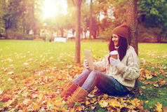 Woman with tablet pc and coffee in autumn park Stock Images