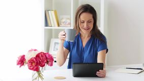 Woman with tablet pc and coffee at home or office stock video footage