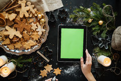 woman with tablet pc computer making gingerbread houses at home Stock Photo