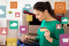 Woman with tablet pc and credit card at home. Tourism, travel, insurance, payment and people concept - happy young woman with tabglet pc computer and credit card Stock Photography