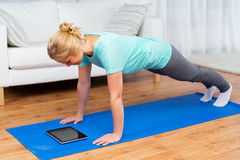 Woman with tablet pc doing plank exercise at home. Fitness, sport, training, technology and people concept - happy woman with tablet pc computer doing plank royalty free stock photo