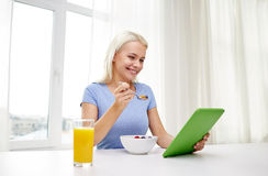 Woman with tablet pc eating breakfast at home Stock Image