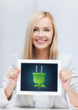 Woman with tablet pc with electrical eco plug Stock Photos