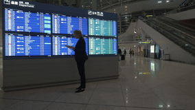 Woman with tablet PC by flight schedule at the airport. Young woman using digital tablet and looking at electronic flight timetable at the airport stock video footage