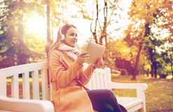 Woman with tablet pc and headphones in autumn park Royalty Free Stock Photos