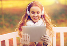 Woman with tablet pc and headphones in autumn park Stock Image