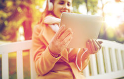 Woman with tablet pc and headphones in autumn park Royalty Free Stock Photography