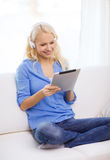 Woman with tablet pc and headphones at home Royalty Free Stock Images