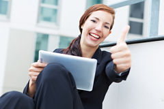Woman with tablet pc holding thumbs Stock Photo