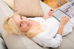 Woman with Tablet pc on the sofa Royalty Free Stock Photography