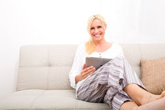Woman with Tablet pc on the sofa Royalty Free Stock Image