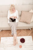 Woman with Tablet pc on the sofa Stock Photo