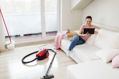 Woman with tablet pc and vacuum cleaner at home. Cleaning, household and technology concept - happy woman or housewife with tablet pc computer and vacuum cleaner Royalty Free Stock Photography