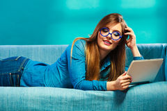 Woman with tablet relaxing on couch blue color Royalty Free Stock Image