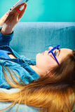 Woman with tablet relaxing on couch blue color Royalty Free Stock Images