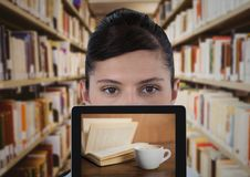 Woman with tablet showing book and coffee against blurry bookshelves Royalty Free Stock Photo