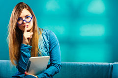 Woman with tablet sitting on couch blue color. Modern technology education internet concept. Fashion woman in glasses with tablet sitting on couch finger on lips Stock Photo