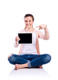 Woman with tablet sitting on the floor, studio shot, isolated Royalty Free Stock Photography