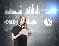 Woman with tablet and six graphs on blackboard Royalty Free Stock Photo