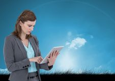 Woman on tablet with sky and grass background Royalty Free Stock Photos