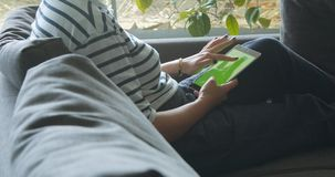 Woman with a tablet on a sofa closeup. Woman with a tablet on a sofa touches it closeup stock footage